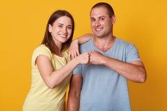 Het studioschot van gelukkig glimlachend jong vrouw en man paar geeft vuistbuil bekijkend camera met boergelaatsuitdrukking, die  stock afbeeldingen