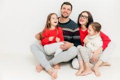 Het studioschot van gelukkige familieleden zit op vloer met naakte voeten, stock foto's