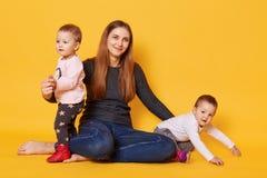 Het studioschot van jonge moeder en haar tweelingpeuters stelt in fotostudio isoleted over gele achtergrond De mama zit met haar stock fotografie