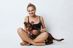 Het studioschot van mooie meisjeszitting kruiste benen met haar hond, die gelukkige uitdrukking hebben terwijl het doorbrengen va Royalty-vrije Stock Foto's