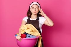 Het studioschot van vermoeide huisvrouw met hoofdpijn, draagt bruine schort en de toevallige witte t-shirt, stelt tegen roze stud royalty-vrije stock fotografie