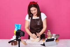 Het studioschot van vrouw kneedt deeg, makend video voor haar culinaire vlog, die tegen camera stellen, vereist wat meer deeg voo stock afbeeldingen