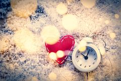 Het stuk speelgoed en de Feelichten van de hartvorm met wekker op sneeuwachtergrond stock fotografie