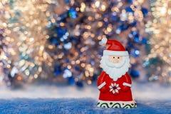 Het stuk speelgoed Santa Claus van het close-upbeeldje op kleurrijk gouden en blauw BO Stock Afbeeldingen
