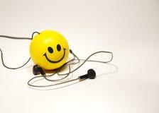 Het stuk speelgoed van de glimlach met de hoofdtelefoons Royalty-vrije Stock Afbeelding