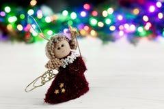 Het stuk speelgoed van de Kerstmisengel op achtergrond van kleurrijke slingerlichten ST Royalty-vrije Stock Foto's