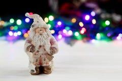 Het stuk speelgoed van de Kerstmiskerstman op achtergrond van kleurrijke slinger ligh Stock Afbeelding