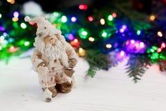 Het stuk speelgoed van de Kerstmiskerstman op achtergrond van kleurrijke slinger ligh Stock Foto