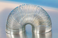 Het Stuk speelgoed van de Lente van het staal op Blauwe MetaalAchtergrond Royalty-vrije Stock Fotografie