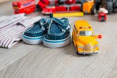 Het stuk speelgoed van de schoolbus dichtbij overhemden en blauwe bootschoenen op grijze houten achtergrond Jongensuitrusting Slu Stock Afbeelding