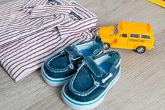 Het stuk speelgoed van de schoolbus dichtbij overhemden en blauwe bootschoenen op grijze houten achtergrond Jongensuitrusting Slu Stock Fotografie
