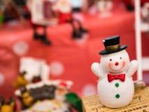 Het stuk speelgoed van de sneeuwmens met de achtergrond van de Kerstmisdecoratie Stock Afbeeldingen