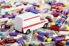 Het stuk speelgoed van de ziekenwagenauto rit door dollars, pillen en  Stock Fotografie