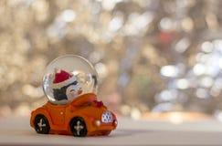 Het stuk speelgoed van glaskerstmis, sneeuwman in een rode auto op een zilverachtige vage achtergrond stock foto