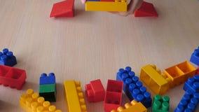 Het stuk speelgoed van het jong geitjeconcept de bouw van plastic bakstenen stock footage