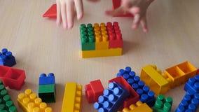 Het stuk speelgoed van het jong geitjeconcept huis van plastic bakstenen stock footage