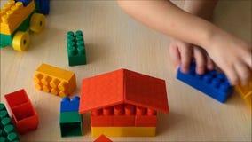 Het stuk speelgoed van het jong geitjeconcept huis van plastic bakstenen stock video