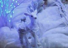 Het stuk speelgoed van het Kerstmisrendier in de sneeuw met lichten Stock Foto