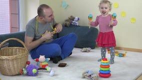 Het stuk speelgoed van het vaderspel gitaar en de schokrammelaar van de babydochter stock videobeelden