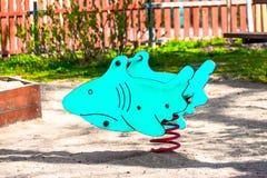 Het stuk speelgoed van kinderen haai, blauwe kleur, op de speelplaats voor kinderen stock foto's