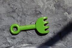 Het stuk speelgoed van kinderen hark op de achtergrond van een concrete plak, stock foto's