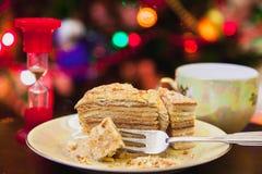 Het stuk van cake ligt op plaat tegen achtergrond van Kerstmis ligh royalty-vrije stock foto