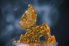 Het stuk van het concentraataka van de cannabisolie verbrijzelt met rook Stock Fotografie