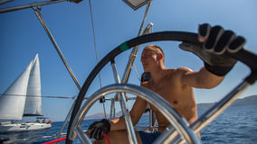 Het stuurwiel van de jonge mensenkapitein tijdens overzees jachtras stock fotografie