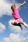 Het succes toont in het opgewekte meisje springen in de lucht Royalty-vrije Stock Afbeeldingen