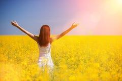 Het succesconcept van de mensenvrijheid Gelukkige vrouw op het gebied met bloemen bij zonnige dag in het platteland De achtergron royalty-vrije stock fotografie