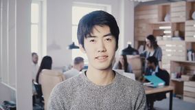 Het succesvolle Aziatische mannelijke startstichter stellen Knappe zakenmanmanager die camera in bezig modern bureau 4K bekijken stock video