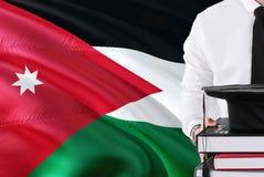 Het succesvolle Jordanian concept van het studentenonderwijs Holdingsboeken en graduatie GLB over de vlagachtergrond van Jordanië royalty-vrije stock foto