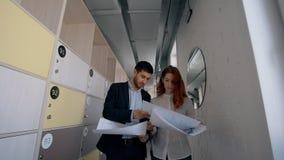 Het succesvolle zakenlui bespreekt blauwdruk, die langs gang van bedrijf gaan stock footage