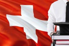 Het succesvolle Zwitserse concept van het studentenonderwijs Holdingsboeken en graduatie GLB over de vlagachtergrond van Zwitserl royalty-vrije stock foto's