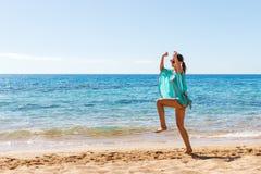 Het succesvrouw van de strandvakantie het springen van vreugde en geluk meisjessprong op een strand op de reis van de zomervakant Stock Foto's