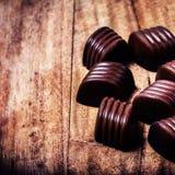 Het suikergoedachtergrond van de close-up bruine chocolade. Chocoladetruffels op houten lijst Stock Foto