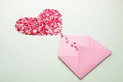 Het suikergoedharten van de snoepjessuiker op envelop over groene achtergrond Royalty-vrije Stock Afbeeldingen