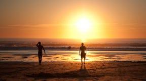 Het surfen bij zonsondergang Stock Afbeeldingen
