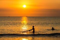 Het surfen bij Zonsondergang Stock Foto's