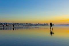 Het surfen de plaats na zonsondergang die een andere iets over sur veronderstelt gelooft naar huis gaan Stock Foto
