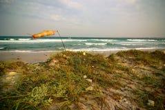 Het surfen van wind-sok op leeg overzees strand tijdens onweer Royalty-vrije Stock Afbeelding