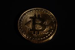 Het symbolische gouden Bitcoin-muntstuk shinning op de donkere achtergrond Stock Foto