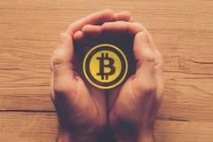 Het symbool van Bitcoincryptocurrency in tot een kom gevormde mannelijke handen royalty-vrije stock foto
