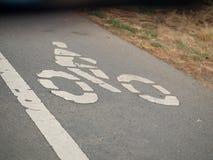 Het symbool van de fietssteeg op asfaltstraat die tot een donkere tunnel leiden stock afbeeldingen
