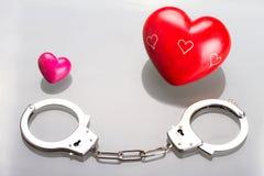 Het symbool van de liefde in handcuffs Stock Foto's