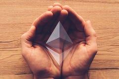 Het symbool van Ethereumcryptocurrency in tot een kom gevormde mannelijke handen stock afbeelding