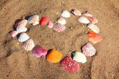 Het symbool van het hart van shells op zand stock fotografie