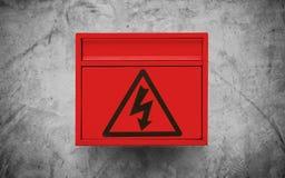 Het symbool van het hoogspanningsteken, op rode elektronische doos op de concrete achtergrond van de muurtextuur Royalty-vrije Stock Afbeelding