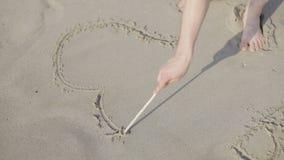 Het symbool van het tekeningshart op een zandig strand stock videobeelden