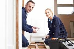 Het Systeem van de de Montagecentrale verwarming van loodgieterand female apprentice stock afbeeldingen